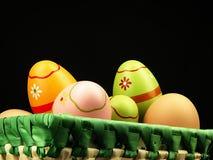 Huevos de Pascua coloridos en la compañía de huevos ordinarios Imagen de archivo