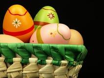 Huevos de Pascua coloridos en la compañía de huevos ordinarios Imágenes de archivo libres de regalías