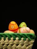 Huevos de Pascua coloridos en la compañía de huevos ordinarios Fotos de archivo libres de regalías