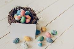 Huevos de Pascua coloridos en la jerarquía y la tarjeta de papel en los vagos de madera de la tabla Foto de archivo libre de regalías