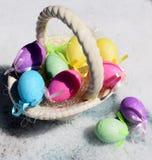Huevos de Pascua coloridos en la nieve Fotos de archivo