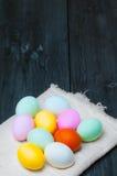 Huevos de Pascua coloridos en la toalla en viejo fondo de madera rústico Imagen de archivo libre de regalías