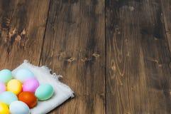 Huevos de Pascua coloridos en la toalla en viejo fondo de madera rústico Fotos de archivo libres de regalías
