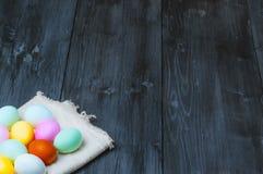 Huevos de Pascua coloridos en la toalla en viejo fondo de madera rústico Foto de archivo libre de regalías