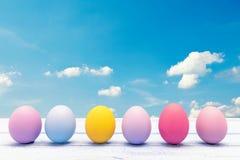 Huevos de Pascua coloridos en un tablero de madera blanco Fotos de archivo