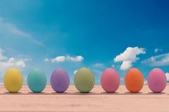 Huevos de Pascua coloridos en un tablero de madera blanco Imagen de archivo