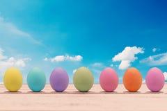 Huevos de Pascua coloridos en un tablero de madera blanco Foto de archivo libre de regalías