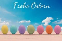 Huevos de Pascua coloridos en un tablero de madera con las letras felices de pascua Imagen de archivo
