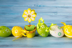 Huevos de Pascua coloridos en un tenedor de la línea y de nota de la flor en fondo de madera azul Fotografía de archivo