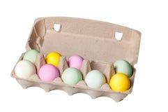 Huevos de Pascua coloridos en una bandeja de la cartulina en el fondo blanco Fotos de archivo libres de regalías