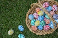 Huevos de Pascua coloridos en una cesta Fotos de archivo