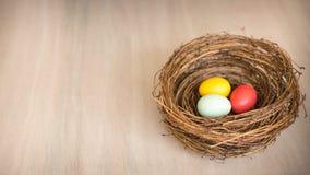 Huevos de Pascua coloridos en una jerarquía o una cesta rústica en backgr de madera Fotografía de archivo