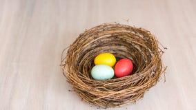 Huevos de Pascua coloridos en una jerarquía o una cesta rústica en backgr de madera Fotos de archivo libres de regalías