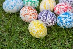 Huevos de Pascua coloridos, fondo de la hierba Imagenes de archivo