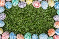 Huevos de Pascua coloridos, fondo de la hierba Imagen de archivo