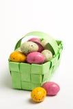 Huevos de Pascua coloridos manchados en una cesta de mimbre verde Imagenes de archivo