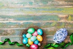 Huevos de Pascua coloridos pintados en jerarquía con las flores del jacinto y la opinión superior de la cinta Fondo festivo para  Fotos de archivo libres de regalías