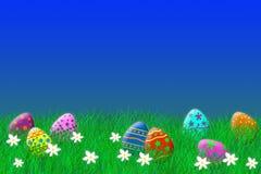 Huevos de Pascua coloridos que ponen en la hierba debajo de un cielo azul fotografía de archivo