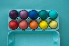 Huevos de Pascua coloridos teñidos mano vibrante en un cartón de huevos de la cartulina visto imagenes de archivo