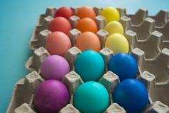 Huevos de Pascua coloridos teñidos mano vibrante en un cartón de huevos de la cartulina visto imágenes de archivo libres de regalías