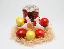 Huevos de Pascua coloridos y dos gallinas del juguete en una jerarquía y una torta de Pascua en el fondo blanco, imagen de la pri fotos de archivo