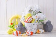 Huevos de Pascua coloridos y pájaros decorativos en el backg de madera blanco fotografía de archivo