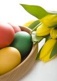 Huevos de Pascua coloridos y tulipanes amarillos Imagen de archivo