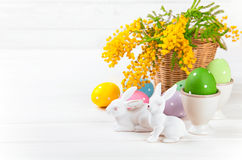 Huevos de Pascua con el conejo y la mimosa de la rama Foto de archivo libre de regalías