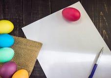 Huevos de Pascua con el documento en blanco y la pluma sobre la tabla de madera Aliste a Imagen de archivo libre de regalías
