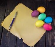 Huevos de Pascua con el documento en blanco y la pluma viejos sobre la tabla de madera rústica Imagen de archivo