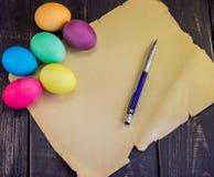 Huevos de Pascua con el documento en blanco y la pluma viejos sobre la tabla de madera Writi Imagen de archivo libre de regalías