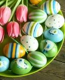 Huevos de Pascua con el ornamento y los tulipanes Fotografía de archivo