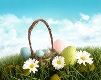 Huevos de Pascua con la cesta en la hierba Fotografía de archivo