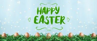 Huevos de Pascua con la Pascua feliz que pone letras en hierba verde, tulipanes con el bokeh y luz del sol en un fondo azul stock de ilustración