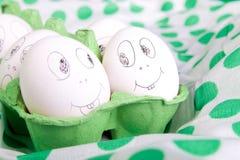 Huevos de Pascua con las caras divertidas en el verde Foto de archivo