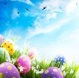 Huevos de Pascua con las flores en hierba en el cielo azul Fotos de archivo