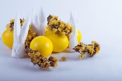 Huevos de Pascua con las flores en un blanco fotos de archivo