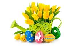 Huevos de Pascua con los tulipanes amarillos en regadera Imagenes de archivo