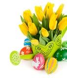 Huevos de Pascua con los tulipanes amarillos en regadera Imagen de archivo