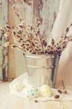 Huevos de Pascua con un ramo de ramas de la primavera de un sauce en un cubo Imagen de archivo
