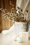 Huevos de Pascua con un ramo de ramas de la primavera de un sauce en un cubo Foto de archivo libre de regalías
