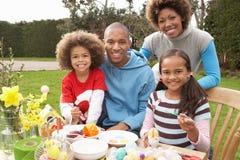 Huevos de Pascua de la pintura de la familia en jardines Foto de archivo libre de regalías