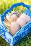 Huevos de Pascua de madera en una cesta azul Fotos de archivo libres de regalías