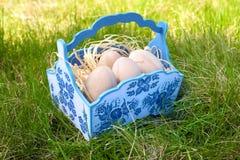Huevos de Pascua de madera en una cesta azul Foto de archivo