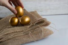 Huevos de Pascua de oro en el fondo rústico blanco Mano que sostiene un huevo Imagenes de archivo