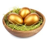 Huevos de Pascua de oro en el tazón de fuente aislado imagen de archivo