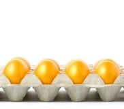Huevos de Pascua de oro en una bandeja en el fondo blanco Fotos de archivo