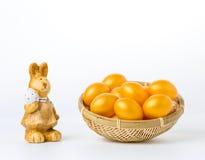 Huevos de Pascua de oro en una cesta en un fondo blanco Foto de archivo