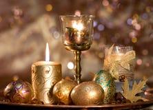 Huevos de Pascua de oro y una vela ardiente imágenes de archivo libres de regalías