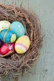 Huevos de Pascua decorativos pintados en fondo de madera imagenes de archivo